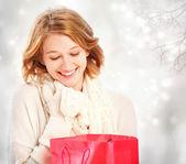 Beautiful young woman looking at a gift bag  — Photo