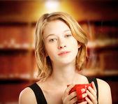 Young woman holding red coffee mug — Zdjęcie stockowe