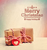 Merry Christmas text with cute little gift boxes — Stock Photo