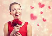 Mladá žena hospodářství červené růže — Stock fotografie