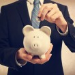 Young man depositing money in piggy bank — Stock Photo #65310595