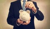 Young man depositing money in piggy bank — Stock Photo