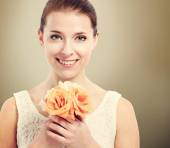 Beautiful young woman holding roses — Stockfoto