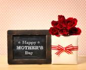Chalkboard with roses and present box — Stock Photo
