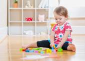 Toddler girl playing with wooden toy blocks — Stock Photo