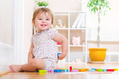 Toddler girl smiling while playing with wooden toy blocks — Stock Photo