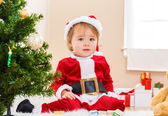 Little girl sitting by the Christmas tree — Stock Photo