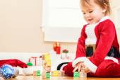 Little girl playing with her Christmas toys — Stock Photo