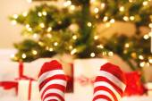 Feet with striped socks with Christmas gift boxes — Stock Photo