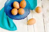 Fresh eggs over white wood — Stock Photo