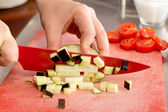 Chef cutting eggplant little cubes over red chopping board — Stock Photo
