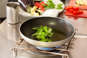 Basil cooking inside pan with raw ingredients in the background — Stock Photo