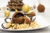 Chocolate bauble with glazed chestnut inside against christmas b — Stock Photo