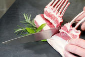 Chef hands cutting lamb cutlet — Zdjęcie stockowe