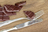 Slices of chocolate bar with silverware — Stock Photo
