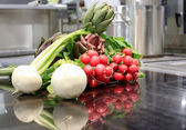 Raw celery head, radish and artichokes over plate induction in a — Stock Photo