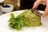 Homemade pasta with rocket pesto and pine nuts crusted squid ink — Stock Photo