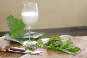 Mixed field greens and fresh milk to the farm — Stock Photo