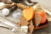 Persimmon, cereal bread, nougat and red wine glass — Stock Photo