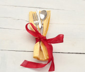 Elegant  vintage silverware inside yallow napkin with red bow — Stock Photo