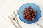Delicious olives inside blue bowl with vintage silverware — Stock Photo