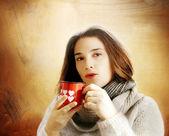 Brunette girl drinking hot beverage gainst golden background — Stock Photo