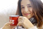 Smiling girl  drinking something from Valentine heart painted gl — Stock Photo