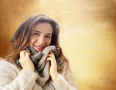 Smiling girl with winter clothes and wool scarf against golden b — Stock Photo