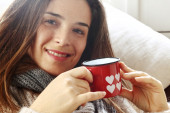 Smiling girl over sofa drinking something from Valentine heart p — Stock Photo