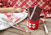Modica chocolate bar inside hearts decorated mug with kitchen ut — Стоковое фото