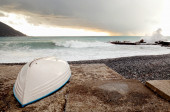 Boat hull to the beach with stormy weather in the background — Stock Photo