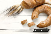 Doughnut bread and cereal french bread over wood — Stock Photo