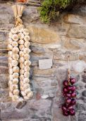 Red onions and garlic string over country wall — Stock Photo