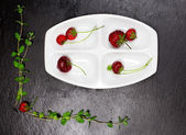 Strawberries inside ceramic plate over black slate background — Stock Photo
