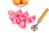 Pink ravioli with eggs and kitchen tools — Stock Photo