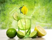 Lime and lemon cocktail over green background — Stock Photo