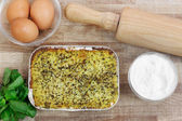 Vegetable savory pie with ingredients and kitchen tools — Stock Photo