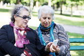 Two mature ladies discovering technology with smart phone — Stock Photo