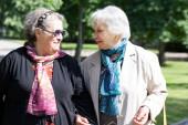 Two senior ladies walking friendly to the park — Stock Photo