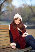 Young girl sitting on bench in a park — Stock fotografie