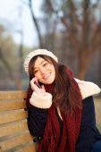 Girl enjoying talking on mobile phone on bench in park — Stock fotografie
