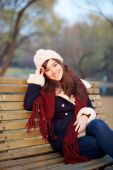 Jeune fille assise sur le banc dans le parc — Photo