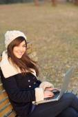 Girl sitting with laptop on bench in park — Stock fotografie