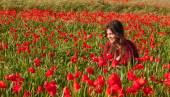Happy smiling teenage girl sitting in a red poppy field — Stock Photo