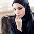 Portrait of the beautiful Muslim woman sitting on an office chair — Stock Photo #64450375