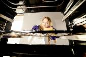 People, housework and housekeeping concept - close up of woman hand in protective glove with rag cleaning oven at home kitchen — Stock Photo