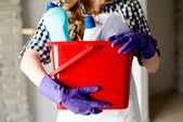 Close-up of woman's hands holding bucket full of cleaners — Stock Photo
