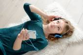 Beautiful young blond woman listening to music — Stock Photo