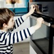Boy dangerously playing with the knobs on the oven — Stock Photo #70261291