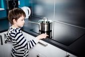 Cute 6 year old boy increases the power of heating  — Stock Photo